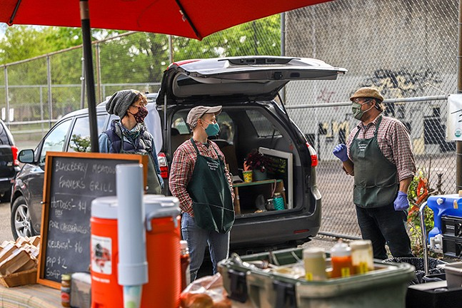 Workers at Bluberry Meadow Farmer's Grill talk behind their booth at a farmers market in East Liberty on May 10 - CP HHOTO: KAYCEE ORWIG