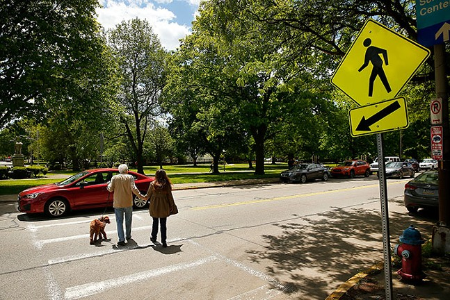 A driver failing to stop as a couple and their dog walk at a crosswalk at Sherman Avenue near the Mexican War Streets in the North Side on Thu., May 13, 2021. - CP PHOTO: JARED WICKERHAM