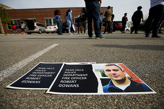 Posters calling for the firing of officer Robert Gowans sit on the ground at a rally and press conference - CP PHOTO: JARED WICKERHAM