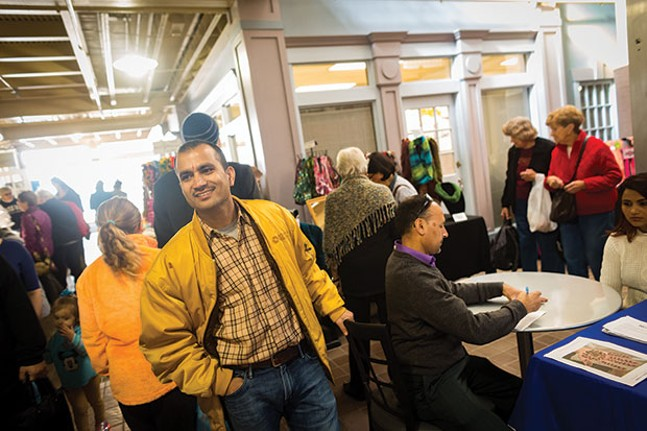 Upendra Dahal organizing a table at a craft show in Caste Village in the South Hills - CP PHOTO BY RENEE ROSENSTEEL