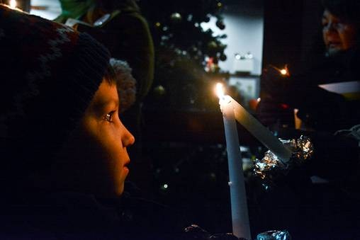 Max Paulat, 6, looks on as his candle is lit outside Jeron X. Grayson Community Center. Anti-gun-violence groups gathered there on the fourth anniversary of the school shooting in Newtown, Conn., to organize and pay respect to the dead. - CP PHOTO BY STEPHEN CARUSO
