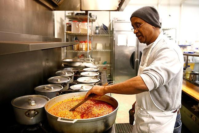 Owner Seifu Haileyesus prepares a sampler of various meats and vegetables at Tana Ethiopian Cuisine in 2008. - CP PHOTO: JARED WICKERHAM