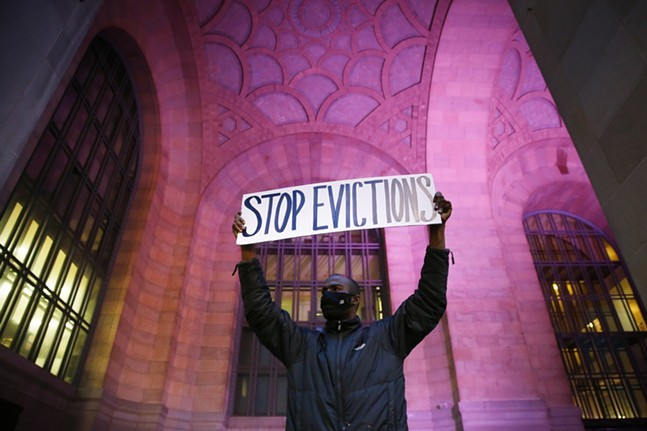 Lou, a Pittsburgh resident facing eviction, holds up a sign during a rally outside of the Pittsburgh's City-County Building in February.