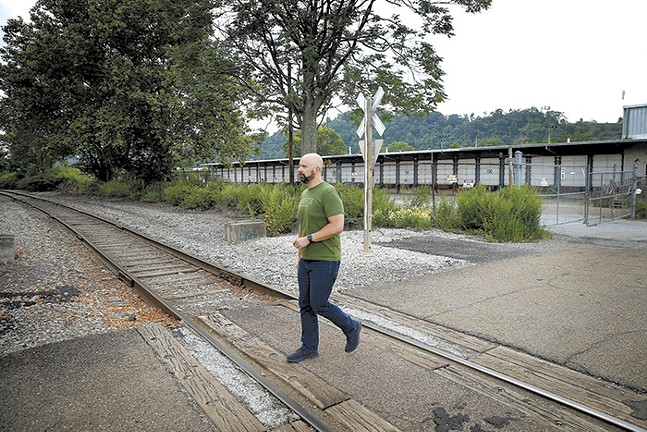 Justin Rossini walks by the proposed Amazon warehouse near his home in Lawrenceville. - CP PHOTO: JARED WICKERHAM