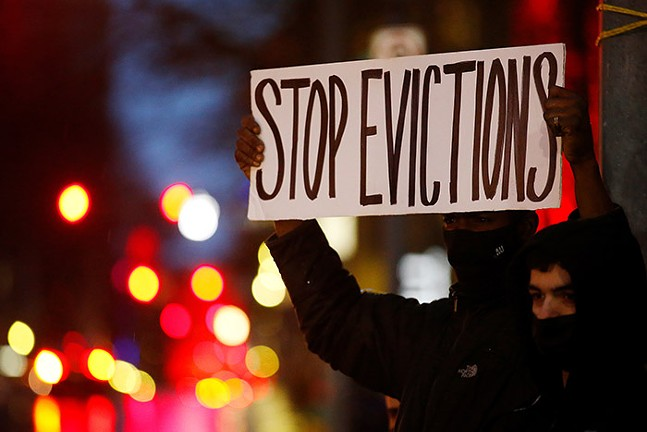 A Pittsburgh resident facing eviction holds up a sign during a rally organized by the Pittsburgh chapter of the United Neighborhood Defense Movement in February 2021. - CP PHOTO: JARED WICKERHAM