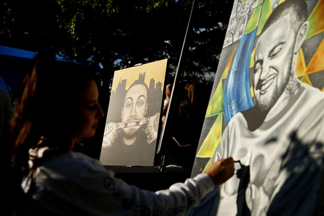 Artist Carlee Overly paints a portrait of Mac Miller at Blue Slide Park. - CP PHOTO: JARED WICKERHAM