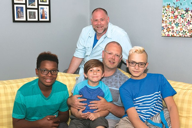 Sean O'Donnell (behind sofa) and his husband Todd Collar (sitting) with their adopted sons A'Sean (left), Elijah (center) and Chris (right) at their home on the North Side - CP PHOTO BY JOHN COLOMBO
