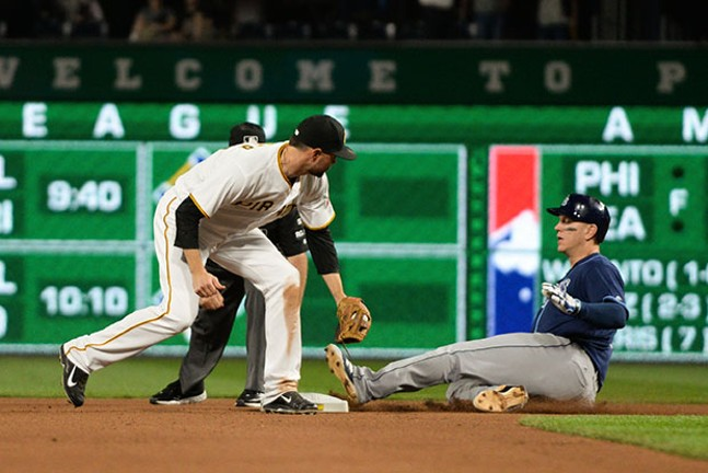 Short stop Jordy Mercer applies a tag a bit late as the Ray's Logan Morrison slides in for a double.