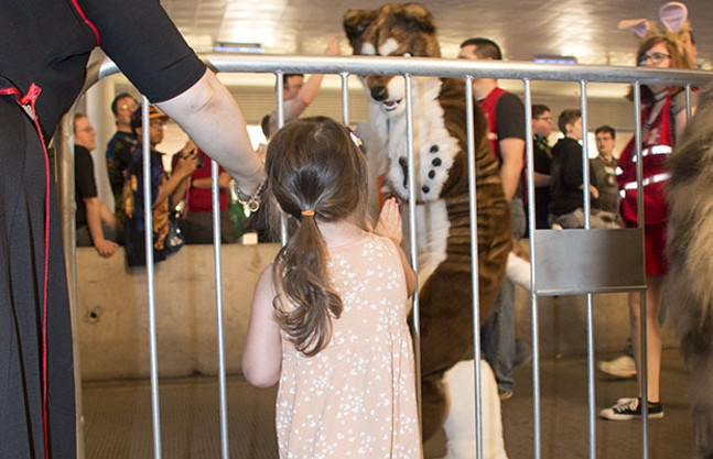 A child waves at a furry during Anthrocon's annual Fursuit Parade on Sat., July 1, 2017. - CP PHOTOS BY JORDAN MILLER