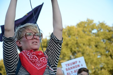 Emily Fear, a DSA member, holds up a speaker to help others hear during the vigil Sunday night. - CP PHOTO BY STEPHEN CARUSO