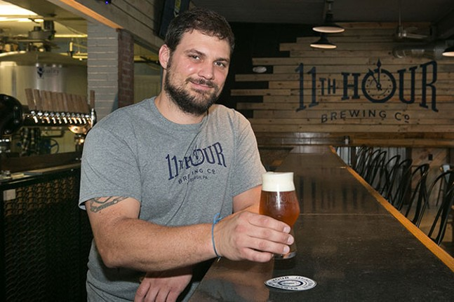 Matt McMahon behind the bar at Eleventh Hour Brewing - CP PHOTO BY JOHN COLOMBO