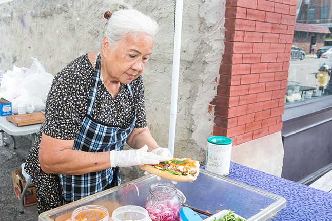 Lucy working at her báhn mì stand - CP PHOTO BY JOHN COLOMBO