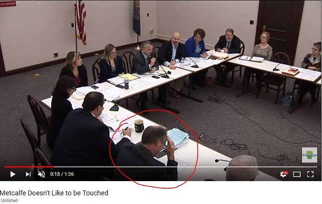 Man who appears to be Republican state Rep. Brett Miller with his face in his hands during a Dec.5 committee meeting in Harrisburg. - IMAGE COURTESY OF YOUTUBE