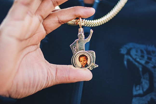 Leon Ford wears a necklace with a picture of his son on one side and a picture of his deceased sister on the other. - CP PHOTO BY CHANCELOR HUMPHREY