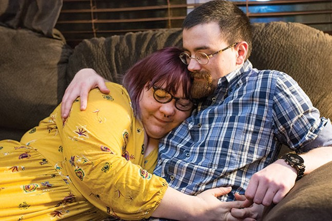 Holden, left, snuggles with fiancé Francis in their home. - CP PHOTO BY JAKE MYSLIWCZYK