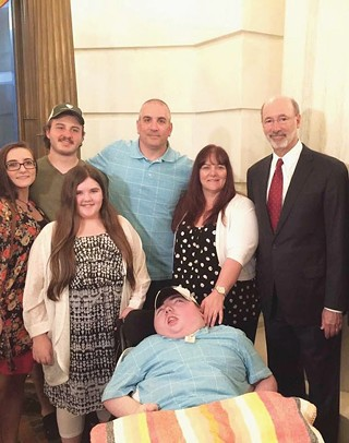 Ryan Briggs and his family pose for a photo with Gov. Tom Wolf the day he signed the medical-marijuana bill into law.
