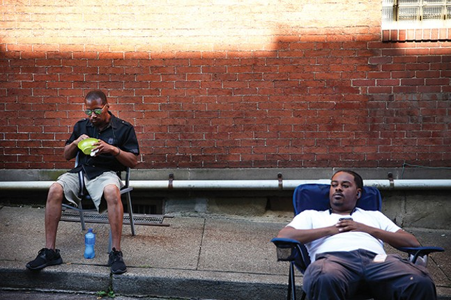 Dan Washington (left) and his friend Wayne (right) hang out along Middle Street.
