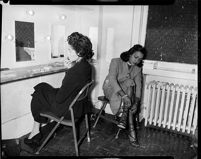 "A history of fashion: Photographer Charles ""Teenie"" Harris' 1954 photograph of Barbara Lee and Delilah Hargrove, cast members of play ""Take a Giant Step,"" in dressing room of Pittsburgh Playhouse - PHOTO COURTESY OF CARNEGIE MUSEUM OF ART, HEINZ FAMILY FUND"