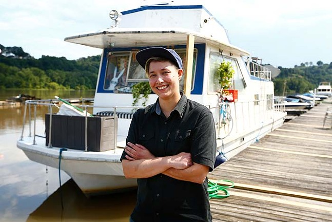 Mia Macdonald with her houseboat along the Allegheny River at the Bell Harbor Yacht Club