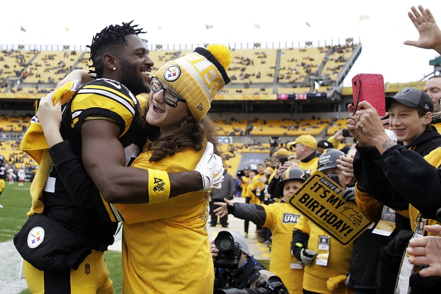 Antonio Brown hugs a fan on the sidelines prior to kickoff against the Cleveland Browns at Heinz Field. - CP PHOTO: JARED WICKERHAM