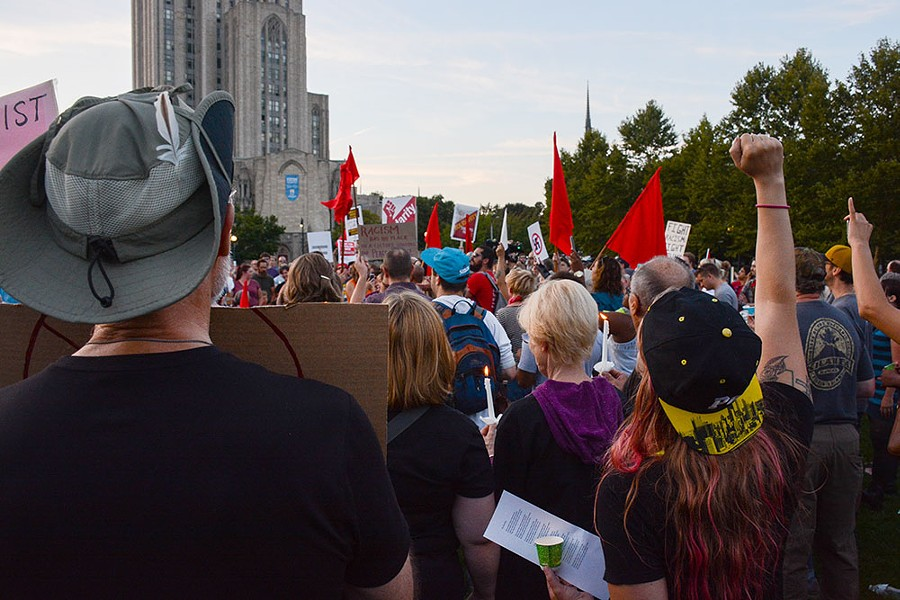 "The crowd sang the 19th century socialist anthem ""The Red Flag"" to the tune of ""O Christmas Tree"" during a candlelight vigil in Schenley Plaza on Sun., Aug. 13. - CP PHOTO BY STEPHEN CARUSO"
