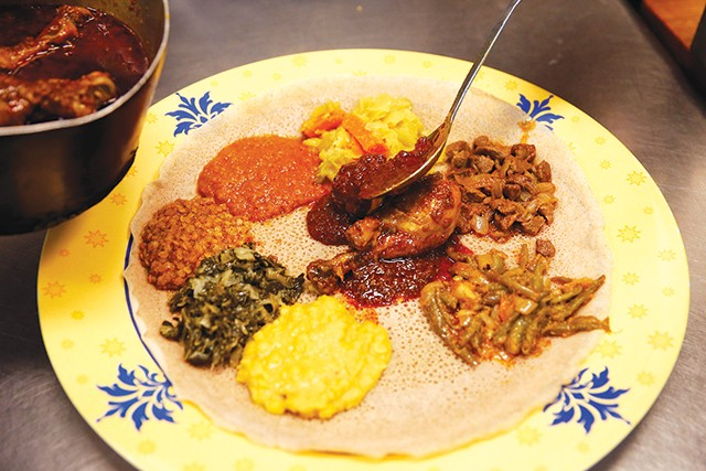 Owner Seifu Haileyesus prepares a sampler of various meats and vegetables. - CP PHOTO: JARED WICKERHAM