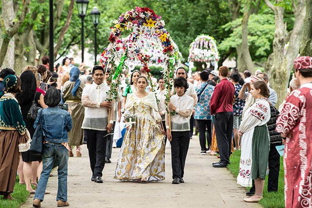 Cerina Wichryk, a member of Oakdale's Filipino community, walks under an archway of flowers. - AIMEE OBIDZINSKI/UNIVERSITY OF PITTSBURGH
