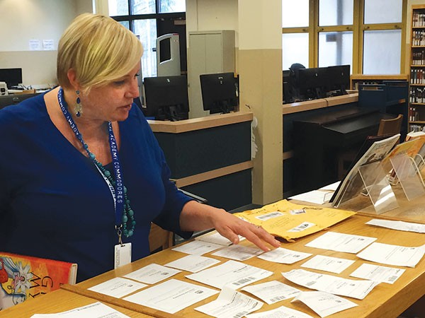 Librarian Sheila May-Stein reviews the dozens of Amazon gift notices she received with donated books. - PHOTO BY ALLAN SMITH