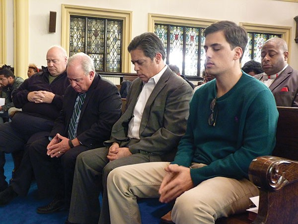 U.S. Congressmen Mike Doyle (second from left) and state Sen. Jay Costa (second from right) bow their heads in a moment of silence for those killed in the Wilkinsburg shootings.