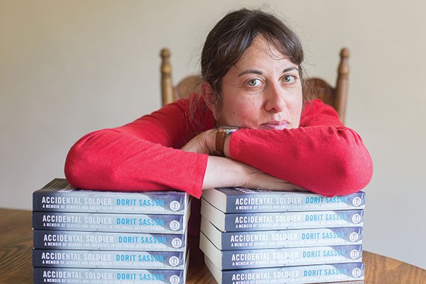 Author Dorit Sasson with copies of Accidental Soldier