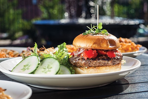Smoky Provolone Bacon Burger, with cherry tomatoes, provolone, bacon, frisee and roasted-garlic aioli
