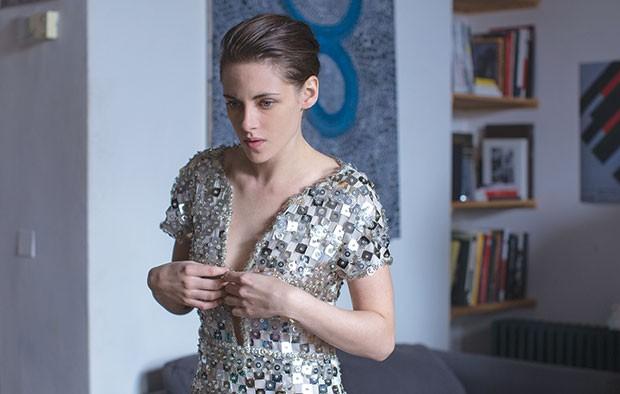Spooked: Maureen (Kristen Stewart) tries on a shiny look.