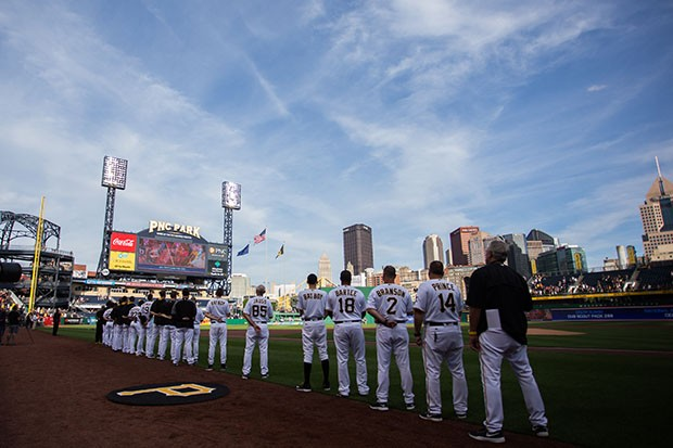 Pirates players stand on the field during the playing of the National Anthem.