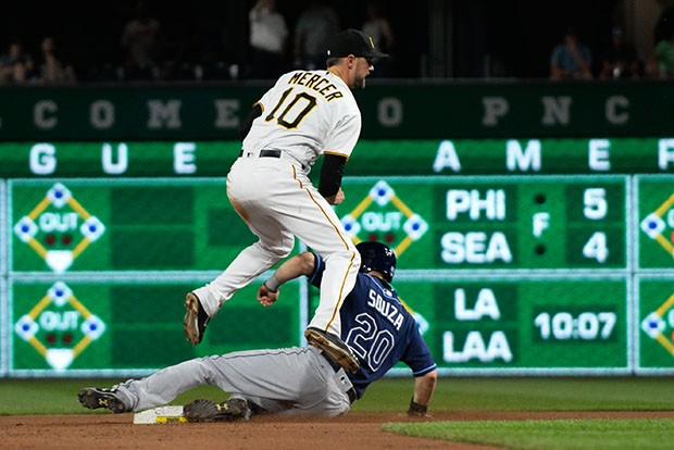 Short stop Jordy Mercer jumps over a sliding Rays player after trying to turn a double play.