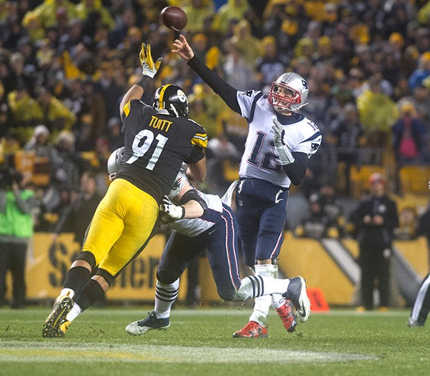 Tom Brady is pressured by Steelers Stephon Tuitt while throwing a pass down the sideline.