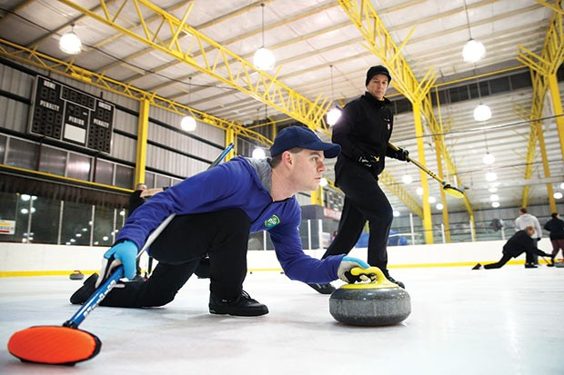 Player preparing to slide stone down curling rink - CP PHOTO BY JARED WICKERHAM