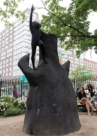 """Rudy Shepherd (costumed) performs atop an earlier version of his sculpture """"Black Rock Negative Energy Absorber,"""" in New York City. - PHOTO COURTESY OF E.F. ROSSARD"""