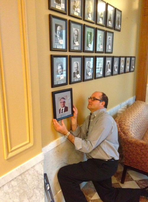 Keith Lachowicz, public arts collection manager at the Regional Arts & Culture Council, hangs up Mayor Sam Adams offiicial portrait.