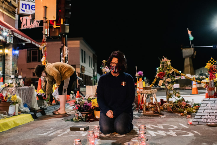 Courtney Ross lays candles at the intersection where her boyfriend, George Floyd, was killed by Officer Derek Chauvin.