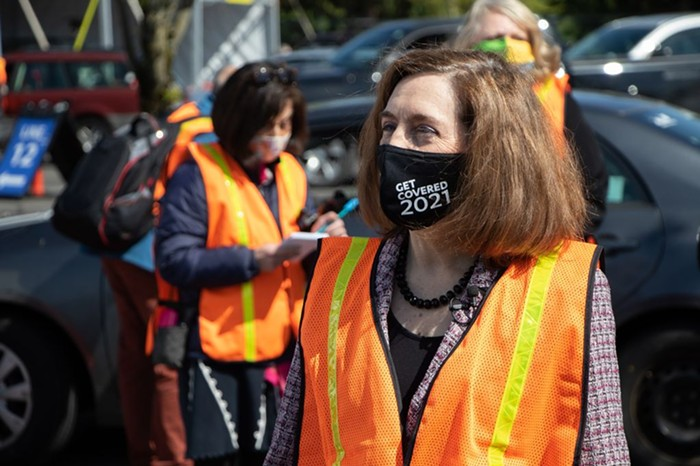 Governor Brown outside wearing an orange vest and black mask that says Get covered 2021