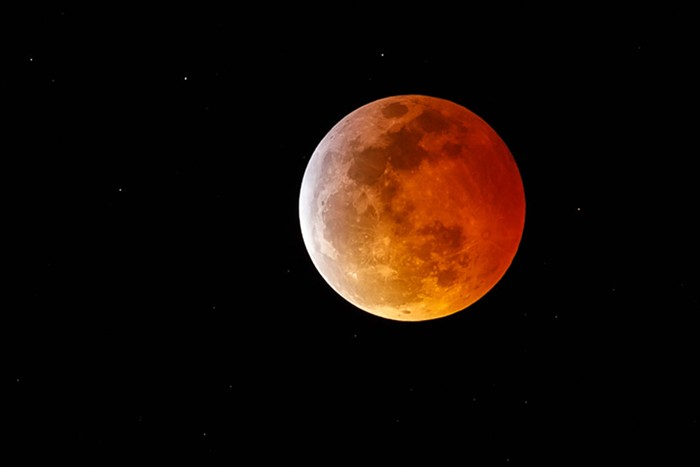 A full moon glowing red during a lunar eclipse.