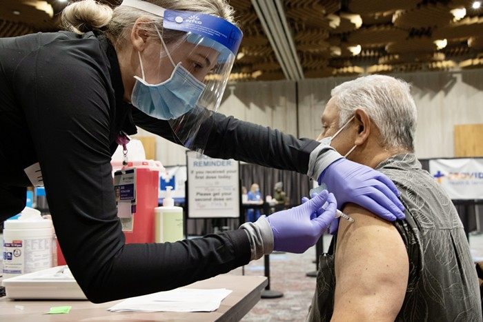 A senior receives a vaccine from a healthcare workers,