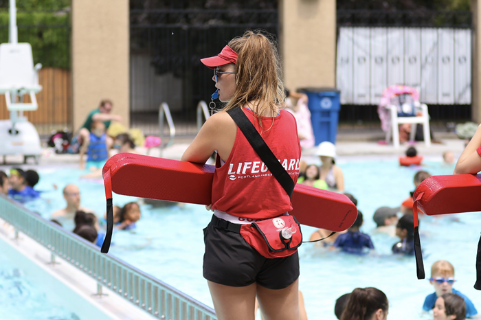 A lifeguard looks over the pool. They have a whistle in their mouth and are holding a flotation device.