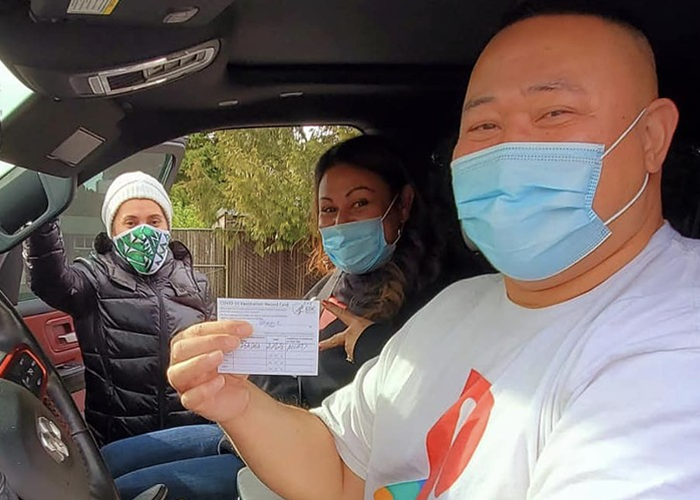 Two Pacific Islander people in a car wearing masks. One of them holds up their vaccination card.