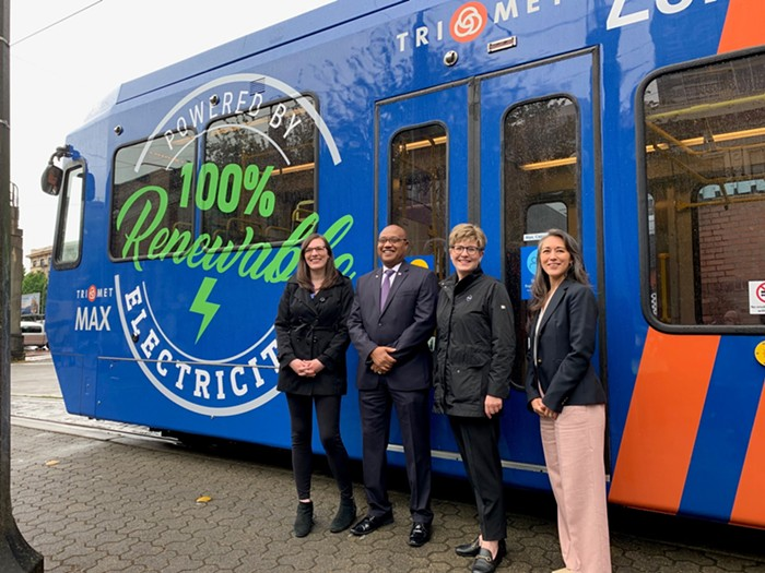 Four people pose in front of an electric bus.