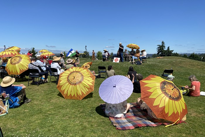 People sit on the grass in front of a cluster of people with a microphone. There are several sunflower umbrellas people are using to shade themselves from the sun.