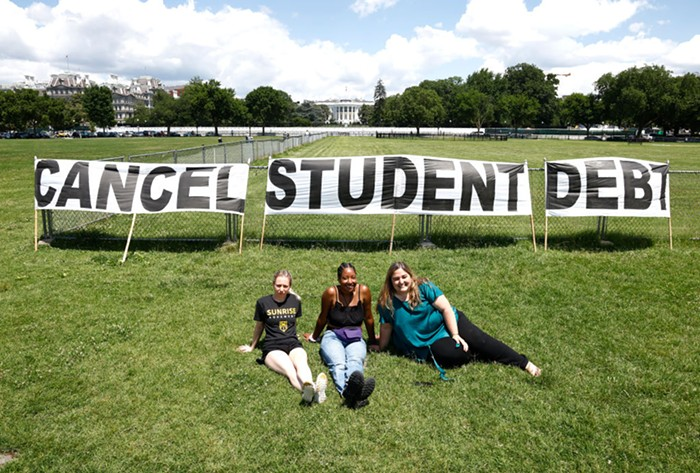 Three people sit in front of a large sign reading cancel student debt