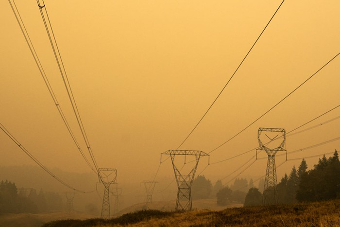 A view of a field with power lines and structures. The sky is orange and the smoke is so dense its hard to see the towers.