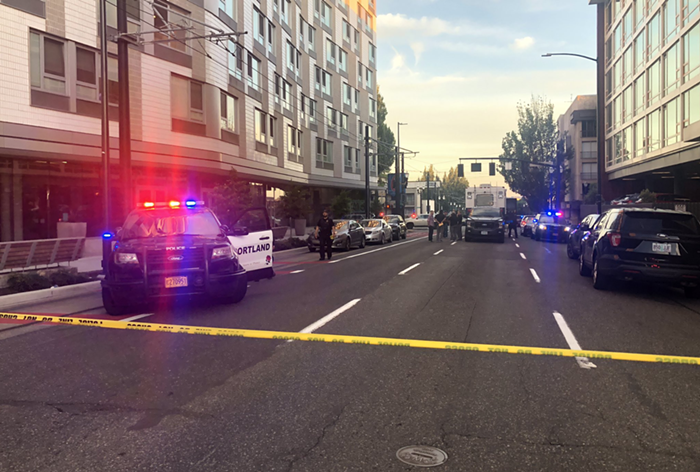 A street with police cars, blocked off with yellow crime scene tape.