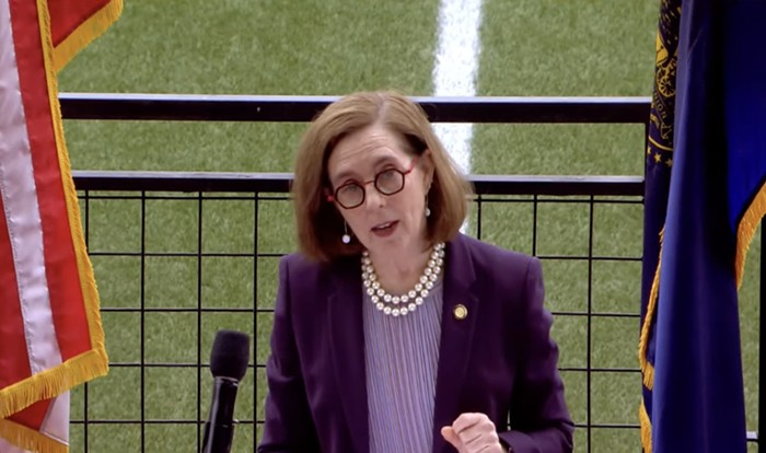 Kate Brown stands behind a podium. She's wearing a purple jacket and talking.